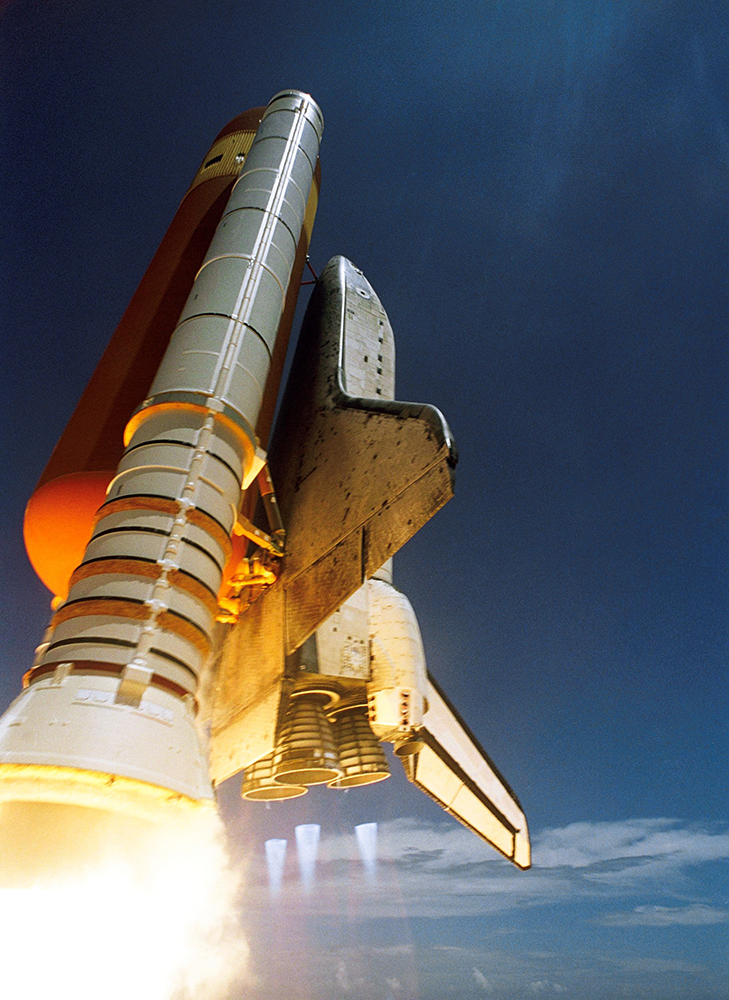 A space shuttle attached to a rocket in the beginning launching phase